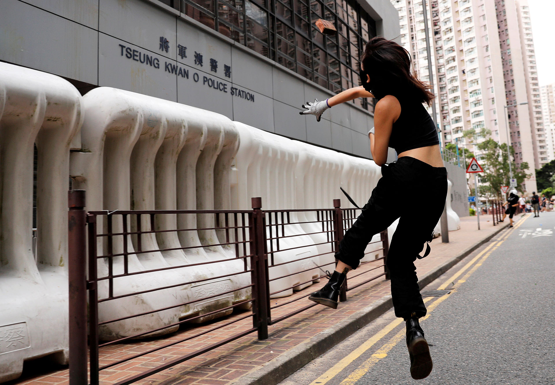 ESCALATION: A protester hurls a brick at a police station in Hong Kong's Tseung Kwan O district in early August. REUTERS/Kim Kyung-Hoon